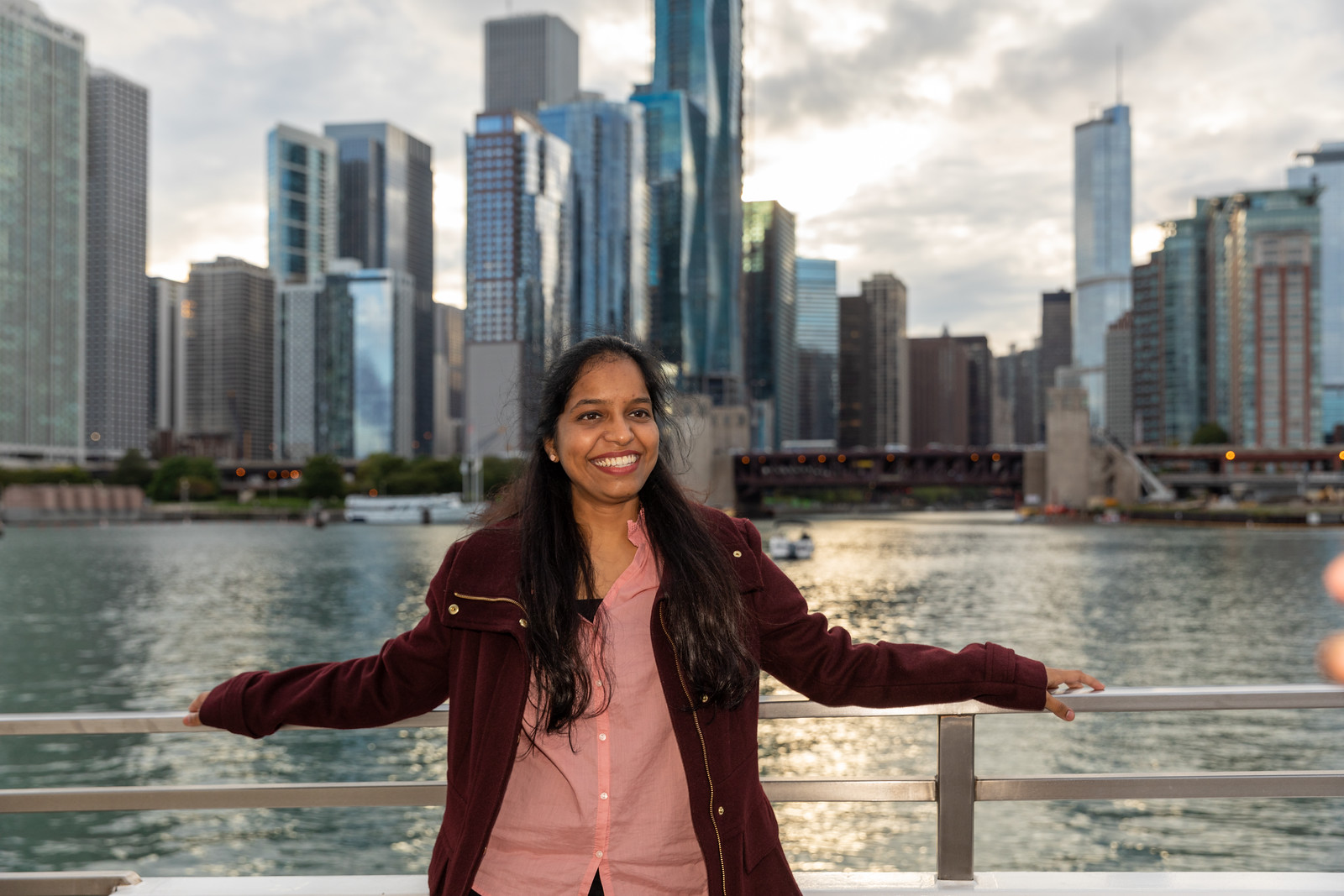 A smiling Roosevelt student standing by the balcony on a Chicago boat tour